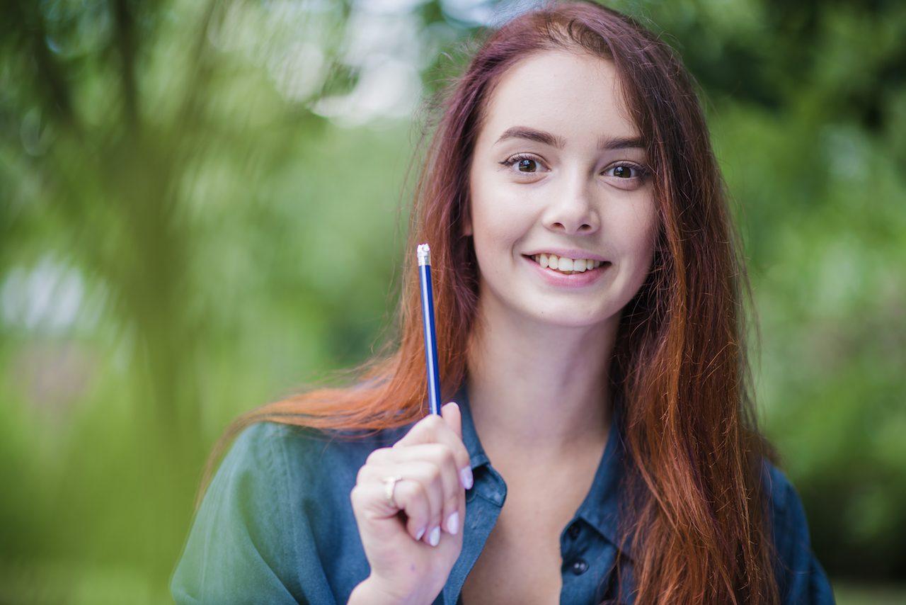 Mujer sonriendo sosteniendo un lápiz